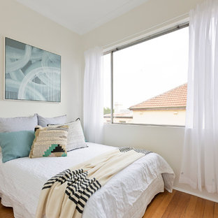 Design ideas for a mid-sized transitional guest bedroom in Sydney with medium hardwood floors, beige walls and brown floor.