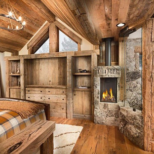 Imagen de dormitorio principal, rústico, grande, con paredes beige, suelo de madera en tonos medios, estufa de leña y marco de chimenea de piedra