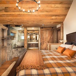 Ispirazione per una camera matrimoniale rustica di medie dimensioni con pareti beige, pavimento in legno massello medio e cornice del camino in pietra