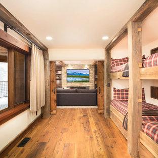 Réalisation d'une grand chambre d'amis chalet avec un mur beige et un sol en bois brun.