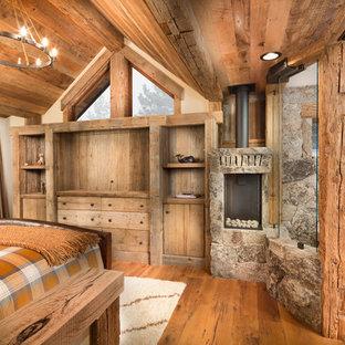 Mittelgroßes Uriges Hauptschlafzimmer mit beiger Wandfarbe, braunem Holzboden, Kaminumrandung aus Stein, Kaminofen und orangem Boden in Sacramento