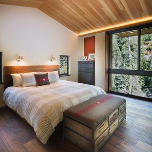 Idée de décoration pour une chambre parentale design avec un mur orange et un sol en bois brun.