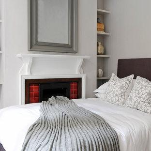 Imagen de habitación de invitados tradicional renovada, pequeña, con paredes grises, chimenea tradicional y marco de chimenea de baldosas y/o azulejos