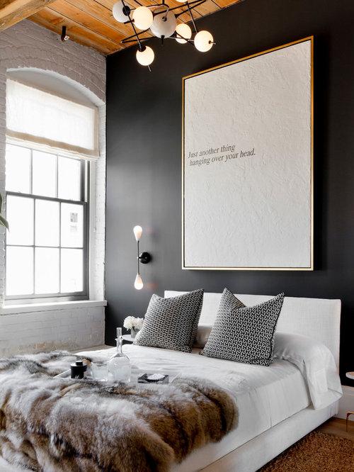 Example of a trendy medium tone wood floor bedroom design in New York with  black walls