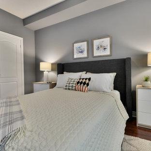 Modelo de dormitorio principal, actual, de tamaño medio, con paredes grises, suelo de madera oscura y suelo rojo
