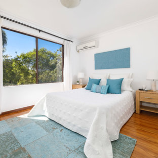 Beach style guest bedroom in Sydney with white walls, medium hardwood floors and brown floor.