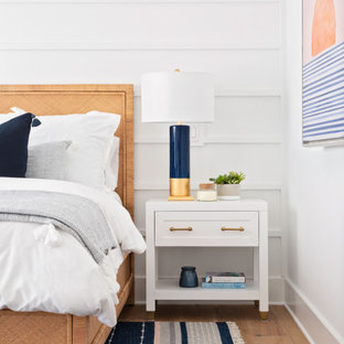Esempio di una camera da letto stile marinaro di medie dimensioni con pareti bianche, pavimento in legno massello medio, pavimento beige e pareti in perlinato