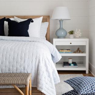 タンパの中くらいのビーチスタイルのおしゃれな主寝室 (白い壁、無垢フローリング、茶色い床、塗装板張りの壁) のインテリア