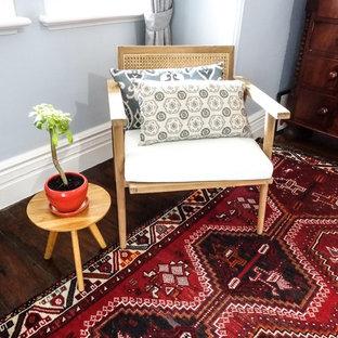 Ejemplo de habitación de invitados campestre, de tamaño medio, con paredes azules, suelo de madera en tonos medios, chimenea de esquina y marco de chimenea de piedra