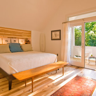 Trendy light wood floor bedroom photo in Other with white walls