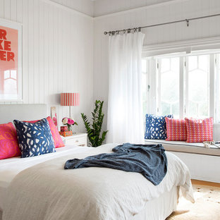 This is an example of a beach style bedroom in Brisbane with white walls, medium hardwood floors and brown floor.