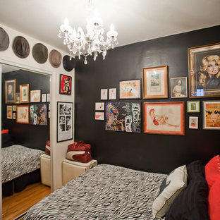 Photo of a small eclectic guest bedroom in New York with black walls, medium hardwood floors, no fireplace and brown floor.