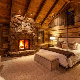 Foto de dormitorio principal, rural, grande, con paredes marrones, chimenea tradicional, marco de chimenea de piedra, suelo de cemento y suelo gris