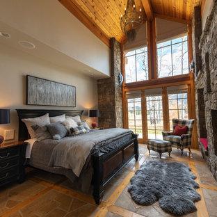 Foto de dormitorio principal, tradicional renovado, grande, con paredes beige, suelo de pizarra, chimenea tradicional, marco de chimenea de piedra y suelo gris