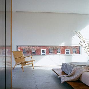 Diseño de dormitorio actual con paredes blancas, suelo de piedra caliza y suelo gris