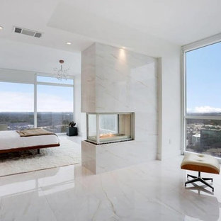 Diseño de dormitorio principal, minimalista, grande, con paredes blancas, suelo de mármol, chimenea de doble cara, marco de chimenea de piedra y suelo blanco