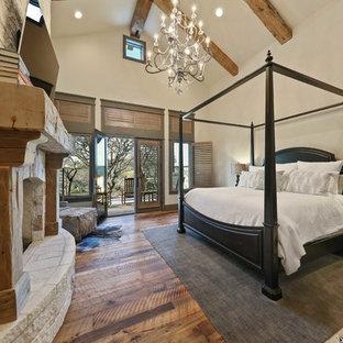 Réalisation d'une très grand chambre parentale chalet avec un mur beige, un sol en bois brun, une cheminée standard, un manteau de cheminée en pierre et un sol marron.