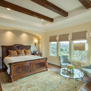 Large mediterranean master bedroom in Austin with beige walls and medium hardwood floors.