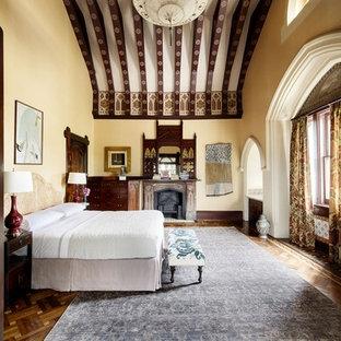 Modelo de dormitorio principal, tradicional, extra grande, con paredes amarillas, suelo de madera en tonos medios, estufa de leña, marco de chimenea de madera y suelo marrón