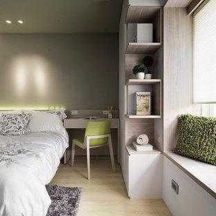Ispirazione per una camera matrimoniale design di medie dimensioni con pareti verdi e pavimento in compensato