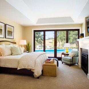 Imagen de dormitorio principal, clásico renovado, extra grande, con paredes beige, moqueta, chimenea tradicional y marco de chimenea de madera