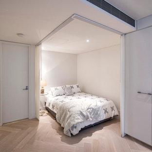 Diseño de dormitorio tipo loft, contemporáneo, pequeño, sin chimenea, con suelo de madera clara