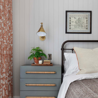 Mid-sized transitional master bedroom in London with grey walls, medium hardwood floors, brown floor and panelled walls.