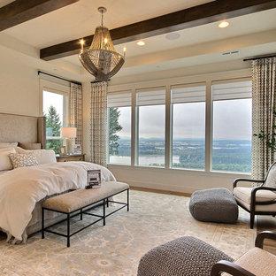 Modelo de dormitorio principal, campestre, extra grande, con paredes beige, suelo de madera clara, chimenea tradicional, marco de chimenea de piedra y suelo marrón