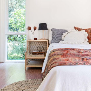 Photo of a beach style bedroom in Wollongong with white walls, medium hardwood floors and brown floor.