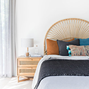 Photo of a beach style bedroom in Wollongong with white walls and white floor.
