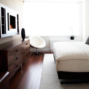 Modern inredning av ett mellanstort huvudsovrum, med vita väggar, mörkt trägolv, en hängande öppen spis, en spiselkrans i metall och brunt golv