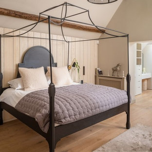 Photo of a coastal master bedroom in Cornwall with beige walls, light hardwood flooring, no fireplace and beige floors.