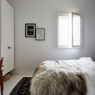 This is an example of a tropical guest bedroom in Sydney with blue walls, painted wood floors and white floor.