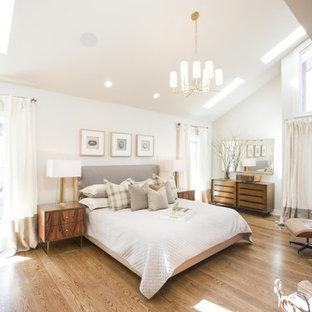 Foto de dormitorio principal, tradicional renovado, grande, con paredes blancas, suelo de madera en tonos medios, chimenea tradicional y marco de chimenea de ladrillo