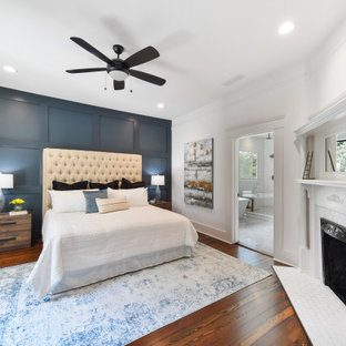 Design ideas for a mid-sized transitional master bedroom in Atlanta with multi-coloured walls, dark hardwood floors, a corner fireplace, a wood fireplace surround and brown floor.