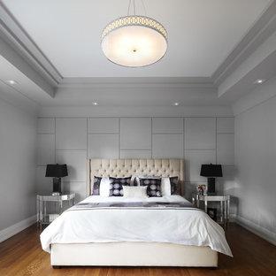 Foto di una camera da letto design con pareti grigie e pavimento in legno massello medio