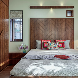 Inspiration for a contemporary bedroom in Pune with green walls, dark hardwood floors and brown floor.