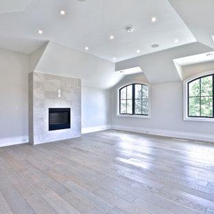 Foto de dormitorio principal, minimalista, grande, con paredes grises, suelo de madera clara, chimenea lineal, marco de chimenea de baldosas y/o azulejos y suelo beige