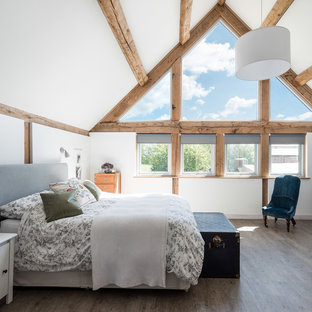 This is an example of a farmhouse bedroom in West Midlands with white walls, medium hardwood flooring and grey floors.