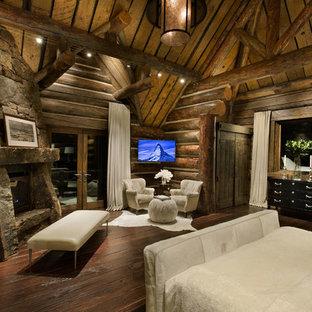 Imagen de habitación de invitados rural, extra grande, con suelo de madera oscura, chimenea de esquina, marco de chimenea de piedra, paredes marrones y suelo marrón