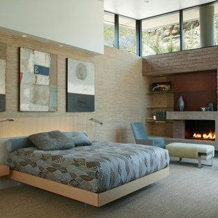 На фото: огромная хозяйская спальня в современном стиле с бежевыми стенами, ковровым покрытием, стандартным камином, фасадом камина из бетона и серым полом с