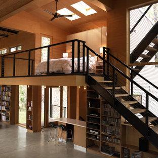 Diseño de dormitorio tipo loft, actual, de tamaño medio, sin chimenea, con paredes marrones, suelo de madera en tonos medios y suelo marrón