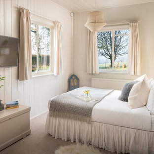 Country bedroom in Hampshire with beige walls, carpet and grey floors.