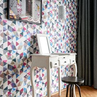 Kleines Modernes Schlafzimmer ohne Kamin mit bunten Wänden, braunem Holzboden und braunem Boden in Berlin