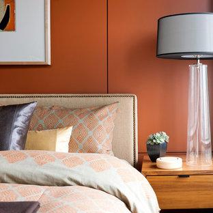 Foto på ett mellanstort funkis huvudsovrum, med orange väggar och ljust trägolv