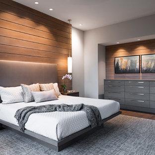 Réalisation d'une grand chambre parentale minimaliste avec un mur beige, aucune cheminée, un sol en bois foncé et un sol marron.
