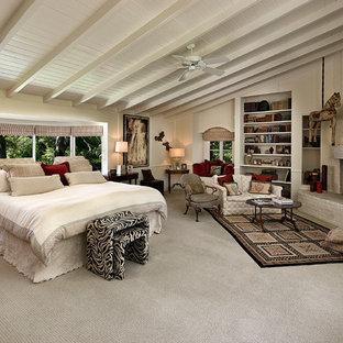 Стильный дизайн: большая хозяйская спальня в средиземноморском стиле с белыми стенами, ковровым покрытием, угловым камином, фасадом камина из кирпича и белым полом - последний тренд