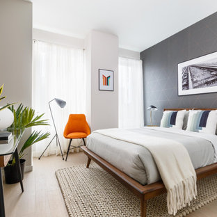 This is an example of a mid-sized contemporary master bedroom in New York with white walls, light hardwood floors, beige floor and wallpaper.