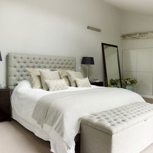 Mid-sized farmhouse master carpeted bedroom photo in London with gray walls