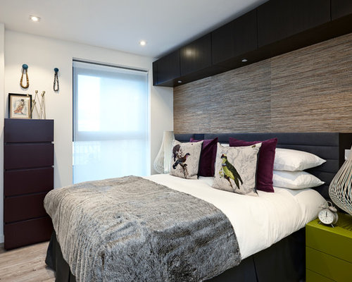 Inspiration for a small contemporary medium tone wood floor bedroom remodel  in London with white walls